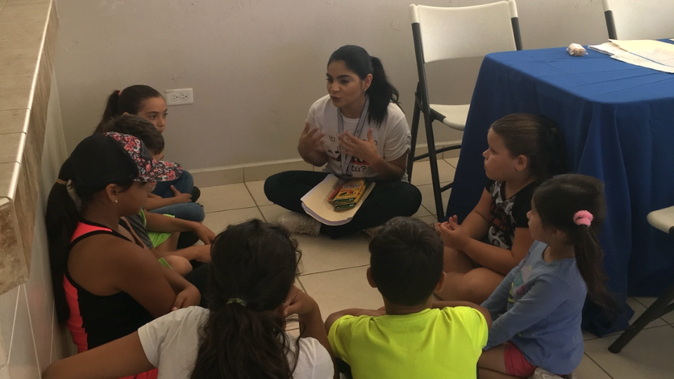 A behavioral health professional with CHF's partner program in Puerto Rico, Salud Integral en la Montaña (SIM) supports a group of children after Hurricane María.